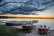 Three beached boats by a dock in Lake Mitchell during orange sunset, at Lakeside Charlies restaurant, near Sun-N-Snow Motel, Cadillac, Michigan, USA.