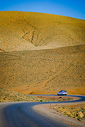 A car makes it's way along a road in southern Morocco near Skours in the lare evening<br /> <br /> (c) Andrew Wilson   Edinburgh Elite media