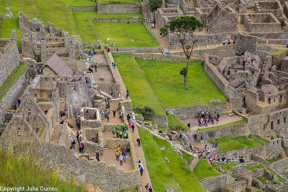 Visitors explore Machu Pichu's stone structure in the Cuscoregion of Peru. The number of daily tourists who visit the site relatively unresricted has put Machu Pichu on the list of endangered archeological sites and the Peruvian government is considering tighter restrictions.