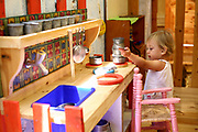 Smiling young girl of two plays with a toy kitchen