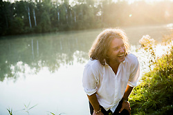 Cheerful man in long hair laughing by river, Bavaria, Germany
