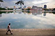 A vietnamese man walks alongside Giang Vo lake, Hanoi, Vietnam, Southeast Asia.