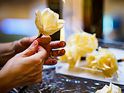 """24 MAY 2017 - BANGKOK, THAILAND: A woman at the Emporium, an upscale shopping mall in Bangkok, makes wooden roses to be used during the cremation of Bhumibol Adulyadej, the Late King of Thailand. In Thai culture it is customary to place wooden flowers in front of a deceased person's coffin or urn as a last tribute before cremation. The Royal Cremation Organisation Committee, which is overseeing plans for the cremation of Bhumibol Adulyadej, the Late King of Thailand, asked the Bangkok Metropolitan Administration (BMA) to provide three million wooden flowers for the late King's cremation. The BMA, in turn, has asked malls and civic organizations to provide flowers. The Mall Group, which owns Emporium, has pledged to provide up to one million wooden """"Wiangping"""" roses, which in Thai culture symbolize unconditional love. The late King will be cremated October 26, 2017.     PHOTO BY JACK KURTZ"""