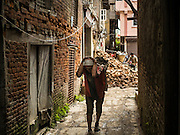 01 AUGUST 2015 - KATHMANDU, NEPAL: A worker in Kathmandu carries bricks out of a home destroyed by the earthquake. The Nepal Earthquake on April 25, 2015, (also known as the Gorkha earthquake) killed more than 9,000 people and injured more than 23,000. It had a magnitude of 7.8. The epicenter was east of the district of Lamjung, and its hypocenter was at a depth of approximately 15 km (9.3 mi). It was the worst natural disaster to strike Nepal since the 1934 Nepal–Bihar earthquake. The earthquake triggered an avalanche on Mount Everest, killing at least 19. The earthquake also set off an avalanche in the Langtang valley, where 250 people were reported missing. Hundreds of thousands of people were made homeless with entire villages flattened across many districts of the country. Centuries-old buildings were destroyed at UNESCO World Heritage sites in the Kathmandu Valley, including some at the Kathmandu Durbar Square, the Patan Durbar Squar, the Bhaktapur Durbar Square, the Changu Narayan Temple and the Swayambhunath Stupa. Geophysicists and other experts had warned for decades that Nepal was vulnerable to a deadly earthquake, particularly because of its geology, urbanization, and architecture.          PHOTO BY JACK KURTZ
