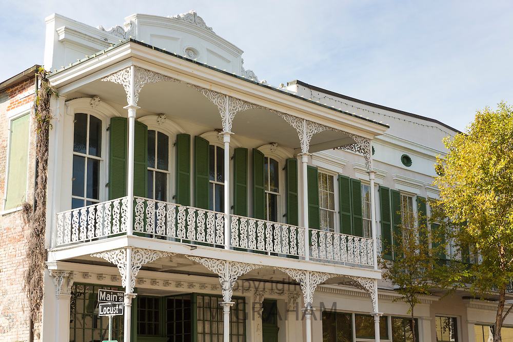 Traditional wrought iron balcony and shutters above shop in Main Street, Downtown Natchez, Mississippi USA