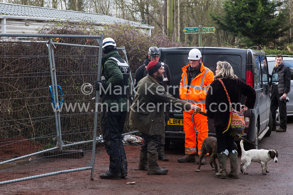 Harefield, UK. 16 January, 2020. By agreement with enforcement agents working on behalf of HS2, Stop HS2 activist Mark Keir brings dogs belonging to Freeman, a fellow activist evicted earlier in the morning from the Harvil Road wildlife protection camp in the Colne Valley after two days spent high up in a tree in woodland, to a friend waiting outside. 108 ancient woodlands are set to be destroyed by the high-speed rail link and further destruction of trees for HS2 in the Harvil Road area is believed to be imminent.