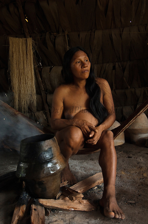 Huaorani Indian woman - Wenyena Baiwa drying her home-made ceramic pot on the fire after washing it out. Gabaro Community. Yasuni National Park.<br /> Amazon rainforest, ECUADOR.  South America<br /> The Huaorani have a unique style of pottery not seen amoung the other Indian groups in the Ecuadorian rain forest.<br /> This is fibre extraced from a palm leaf. It is boiled and sun bleached before being made into string. The thickness depends on usage. Thin string is used for shigras - string bags and thicker string for hammocks.<br /> This Indian tribe were basically uncontacted until 1956 when missionaries from the Summer Institute of Linguistics made contact with them. However there are still some groups from the tribe that remain uncontacted.  They are known as the Tagaeri & Taromenani. Traditionally these Indians were very hostile and killed many people who tried to enter into their territory. Their territory is in the Yasuni National Park which is now also being exploited for oil.