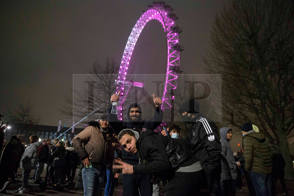 © Licensed to London News Pictures.01/01/2021, London, UK. Members of the public marking the end of the year at South Bank in central London, drinking in the streets as three quarters of England plunged into Tier 4 last night. This New Year's Eve Londoners need to stay at home according to Tier 4 guidelines. Photo credit: Marcin Nowak/LNP