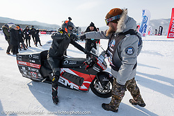 Chief starter Sean Jordan of Utah wishes Mikhail Mikhin a good run on the mile track on the Moscow Polytechnic University electric motorcycle racer that was built for the Baikal Mile Ice Speed Festival. Maksimiha, Siberia, Russia. Saturday, February 29, 2020. Photography ©2020 Michael Lichter.