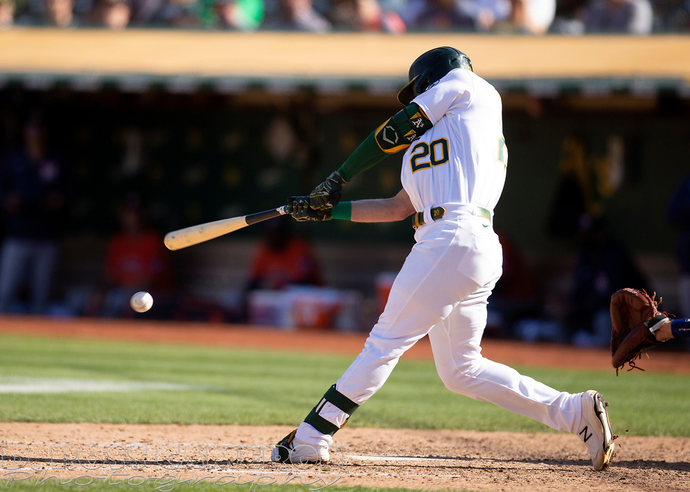 Sep 26, 2021; Oakland, California, USA; Oakland Athletics left fielder Mark Canha (20) connects for an RBI single against the Houston Astros in the seventh inning at RingCentral Coliseum. Mandatory Credit: D. Ross Cameron-USA TODAY Sports
