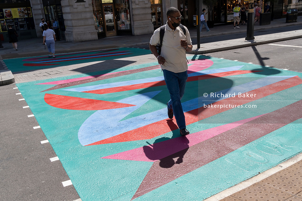 A male pedestrian crosses the multi-coloured markings of a crossing at the junction of Piccadilly and Piccadilly Circus, on 16th July 2021, in London, England.