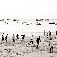 "Stone Town, Zanzibar 03 November  2010<br /> A football match on the beach of Stone Town.<br /> Stone Town or Mji Mkongwe, in Swahili meaning ""ancient town"", is the old part of Zanzibar City, the capital of the island of Unguja, informally known as Zanzibar, part of Tanzania. The town was the centre of trade on the East African coast between Asia and Africa before the colonization of the mainland in the late 19th century after which the focus moved to Mombasa and Dar es Salaam. From 1840 to 1856, Said bin Sultan had the capital of the Omani Empire in Stone Town. The main export was spices and particularly cloves. For many years Stone Town was a major centre for the slave trade; slaves were obtained from mainland Africa and traded with the Middle East. The town also became a base for many European explorers, particularly the Portuguese, and colonizers from the late 19th century. David Livingstone used Stone Town as his base for preparing for his final expedition in 1866. A house, now bearing his name, was lent by Sultan Seyyid Said. Immigrant communities from Oman, Persia and India lived here. <br /> Photo: Ezequiel Scagnetti"