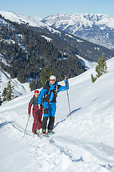 Skiers walking up on snowy mountain