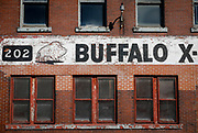 SHOT 10/24/17 10:06:41 AM - Peeling and faded Buffalo signage at Buffalo X-Ray in downtown Buffalo, N.Y. Buffalo, N.Y. is the second most populous city in the state of New York and is located in Western New York on the eastern shores of Lake Erie and at the head of the Niagara River. By 1900, Buffalo was the 8th largest city in the country, and went on to become a major railroad hub, the largest grain-milling center in the country and the home of the largest steel-making operation in the world. The latter part of the 20th Century saw a reversal of fortunes: by the year 1990 the city had fallen back below its 1900 population levels. (Photo by Marc Piscotty / © 2017)