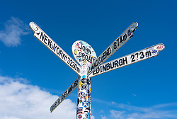 Signpost with distances at John O' Groats on  the North Coast 500 scenic driving route in northern Scotland, UK