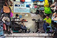 YANGON, MYANMAR - CIRCA DECEMBER 2013: Merchants repairing and selling bags in street market of Yangon