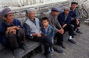 A young Bai boy amongst elder Bai tribesmen (dress in traditional blue), Lijiang, Yunnan, China