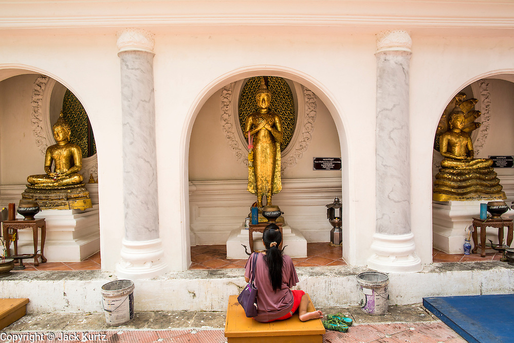 12 OCTOBER 2012 - NAKHON PATHOM, NAKHON PATHOM, THAILAND: A woman prays at Buddha statues Phra Pathom Chedi in Nakhon Pathom. The Phra Pathom Chedi in Nakhon Pathom was commissioned by King Mongkut and completed by King Chulalongkorn in 1870. The chedi is 127 meters tall and is one of the tallest pagodas in the world. It is located in the center of the city of Nakhon Pathom and has been an important Buddhist center since the 6th century. According to local history, Nakhon Pathom is where Buddhism first came to Thailand.     PHOTO BY JACK KURTZ