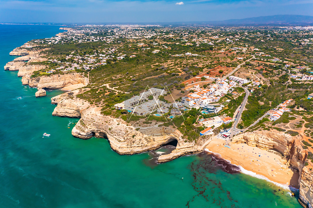 Aerial view of the coastline with the cliffs and the turquoise water near Benagil cave in Lagoa, Algarve, Portugal.