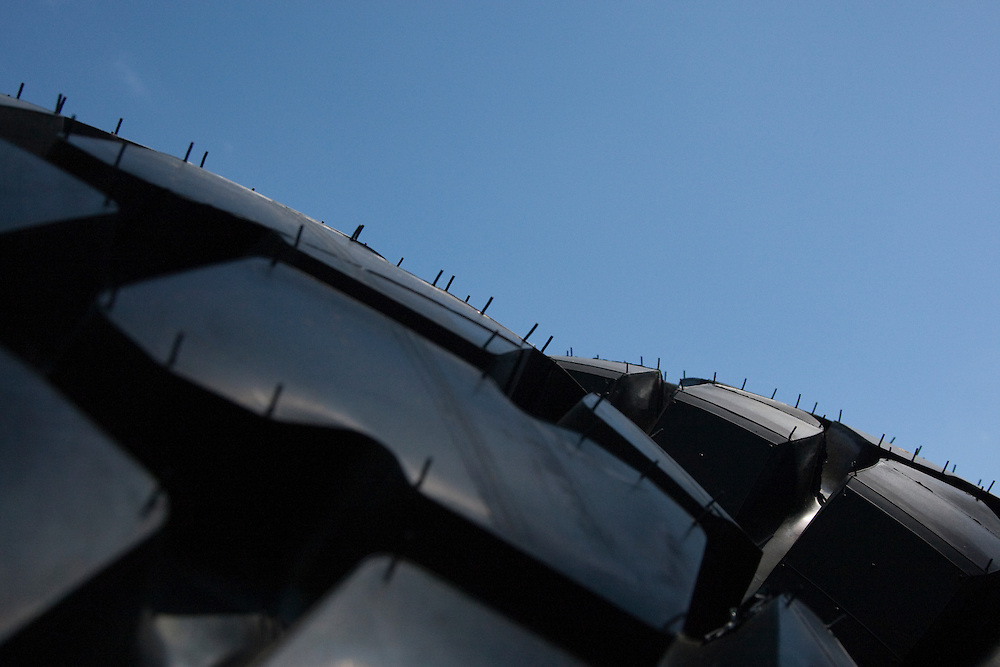 Close up of large tyres and tread with blue summer sky in the background