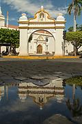 View of a gate at Parque de La Merced and the exterior of La Merced church, Leon, Nicaragua