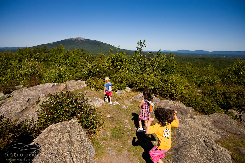 Kids hiking on Gap Mountain in Troy, New Hampshire. Mount Monadnock is in the distance.