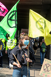 © Licensed to London News Pictures. 01/09/2020. London, UK. A members of Extinction Rebellion (XR) environmental campaign group waves a flag as XR march to Parliament Square in central London ahead of their planned blockade of Parliament. XR plan to peacefully disrupt the UK Parliament with actions planned over two weeks, until MP's back the Climate Ecological Emergency Bill and prepare for crisis with a National Citizens's Assembly. Photo credit: Alex Lentati/LNP