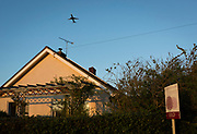 A jet airliner departing from nearby Bristol airport takes-off from a rural bungalow, recently sold by a local north Somerset estate agency, on 5th May 2018, in Wrington, North Somerset, England.