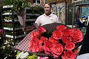 East London June 09 . Columbia Rd flower market. Man selling roses.