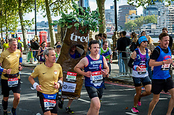 © Licensed to London News Pictures. 03/10/2021. LONDON, UK. A runner in a tree costume on Embankment passes mile 25 in the London Marathon, the first time it has been held since April 2019 due to the Covid-19 pandemic.  Over 36,000 elite athletes, club runners and fun runners are taking part in the mass event, with another 40,000 people taking part virtually.  Photo credit: Stephen Chung/LNP