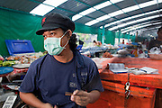 Sept. 23, 2009 -- BANGKOK, THAILAND: A man repairs fishing nets in his stall in Khlong Toey Market in Bangkok, Thailand. Khlong Toey Market is the largest market in Bangkok. Vendors sell everything from meat and fish to fruit and vegetables. They also sell clothes and dry goods in the market. Many working class Thais shop for food everyday because they don't have refrigerators and can't store food at home.   Photo by Jack Kurtz