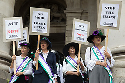 Environmental activists from Extinction Rebellion dressed as suffragettes assemble in front of the Mansion House for a Blood Money March through the City of London on 27th August 2021 in London, United Kingdom. Extinction Rebellion were intending to highlight financial institutions funding fossil fuel projects, especially in the Global South, as well as law firms and institutions which facilitate them, whilst calling on the UK government to cease all new fossil fuel investment with immediate effect.