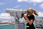 11 year old child looking through coin-operated binoculars aboard the USS Missouri. Battleship Missouri Memorial, Pearl Harbour, Hawaii