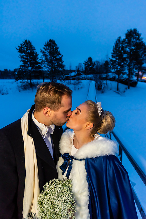 A Norwegian newlywed couple kissing outside in a  winter wonderland before their wedding reception, Trysil, Norway.