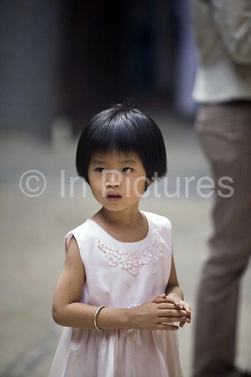 A child at the Thien Hau Pagoda, Ho Chi Minh City (formerly Saigon), Vietnam