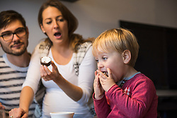 Little boy eating dessert with mouth wide open while parents are shocked, Munich, Germany
