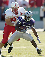 Running back Darren Sproles (43) of Kansas State, runs past Nebraska defensive end Adam Carriker (90) for a first down early in the first quarter at KSU Stadium.  The Wildcats defeated the Cornhuskers 45-21 in Manhattan, Kansas, Oct. 23, 2004.