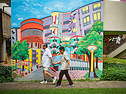 """27 DECEMBER 2016 - SINGAPORE: Shoppers walk past a mural in the Tiong Bahru Market. Tiong Bahru Market in Singapore is popular with local people who live in the community and expatriots living in Singapore. Market vendors sell a lot of imported foodstuffs and the food """"hawker"""" area is one of the most popular in the city.      PHOTO BY JACK KURTZ"""