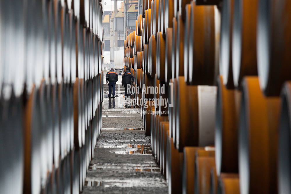Port workers walking through piles of gas pipe destined for the abandoned South Stream gas pipeline, in the port of Burgas, Bulgaria. Photo by Rob Arnold
