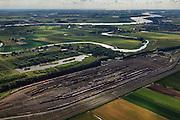Nederland, Zuid-Holland, Zwijndrecht, 15-07-2012; Kijfhoek, rangeerterrein voor goederentreinen. Overzicht van de verdeelsporen met rechts in beeld de railremmen. Richting riviertje de Devel en aan de horizon de Oude Maas..Kijfhoek huisvest Keyrail, exploitant Betuweroute en is in beheer bij ProRail. De Betuweroute, die begint als Havenspoorlijn op de Maasvlakte, verbindt via Kijfhoek de Rotterdamse haven met het achterland. Het rangeeremplacement dient voor het sorteren van goederenwagons waarbij gebruik gemaakt wordt van de zwaartekracht, het 'heuvelen': de wagons worden de heuvel opgeduwd, bij het de heuvel afrollen komen ze, door middel van wissels, op verschillende verdeelsporen. Railremmen zorgen voor het automatisch remmen van de wagons. Na het heuvelproces staan de nieuw samengestelde treinen op aparte opstelsporen..Kijfhoek, railway yard used by ProRail and Keyrail (Betuweroute operator). Kijfhoek connects via the Betuweroute (beginning as Havenspoorlijn on the Maasvlakte), through the port of Rotterdam with the hinterland. The shunting yard for sorting wagons makes use of gravity. The new trains are assembled on separate tracks..luchtfoto (toeslag), aerial photo (additional fee required).foto/photo Siebe Swart