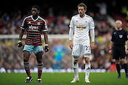 Alex Song of West Ham United (l) and Gylfi Sigurdsson of Swansea City look on. Barclays Premier league match, West Ham Utd v Swansea city at the Boleyn ground, Upton Park in London on Sunday 7th December 2014.<br /> pic by John Patrick Fletcher, Andrew Orchard sports photography.