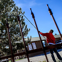 011014       Cable Hoover<br /> <br /> Milo Andablo uses an extendable trimmer to prune a tree in front of his home in Gallup Saturday. Andablo said he had started removing his holiday decorations when he noticed the tree could use a touch-up.