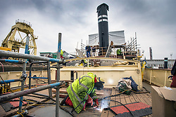 """© Licensed to London News Pictures. 04/05/2016. Birkenhead UK. Picture shows restoration work being carried out on the Daniel Adamson at Camel Laird docks in Birkenhead. The Daniel Adamson steam boat has been bought back to operational service after a £5M restoration. The coal fired steam tug is the last surviving steam powered tug built on the Mersey and is believed to be the oldest operational Mersey built ship in the world. The """"Danny"""" (originally named the Ralph Brocklebank) was built at Camel Laird ship yard in Birkenhead & launched in 1903. She worked the canal's & carried passengers across the Mersey & during WW1 had a stint working for the Royal Navy in Liverpool. The """"Danny"""" was refitted in the 30's in an art deco style. Withdrawn from service in 1984 by 2014 she was due for scrapping until Mersey tug skipper Dan Cross bought her for £1 and the campaign to save her was underway. Photo credit: Andrew McCaren/LNP ** More information available here http://tinyurl.com/jsucxaq **"""