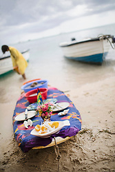 Surfing board decorated as a table with plates, food and flowers, Mauritius