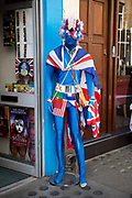 Union Jack Flag man standing outside a fancy dress shop on Berwick Street in Soho, London, UK> This showroom dummy dressed up in a morph suit with various flags, and a wig stands at the door to this dressing up store.