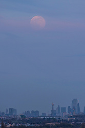© Licensed to London News Pictures. 07/04/2020. LONDON, UK.  A Pink supermoon rises through the haze above central London as seen from Northala Fields, to the west of the capital.  Native Americans gave this month's full moon the name Pink to coincide with the spring blossom of 'moss pink' or phlox flowers.  The moon is at its closest point, the perigee, to Earth during its monthly orbit appearing 30% brighter and 14% larger, hence is known as a supermoon.  Photo credit: Stephen Chung/LNP