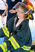 Happy girl age 6 dressed in firefighter gear at fire emergency demonstration. Aquatennial Beach Bash Minneapolis Minnesota USA
