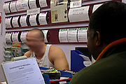 A prisoner discussing available jobs within the prison at the job centre of Coldingley prison..HMP Coldingley, Surrey was built in 1969 and is a Category C training prison. Coldingley is focused on the resettlement of prisoners and all prisoners must work a full working week within the prison. Its capacity is 390 prisoners.