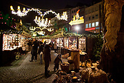 A young boy and his father look around the Christmas market Markt der Engel / Angel Market on Neumarkt, Cologne.