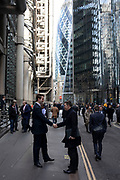 City workers greet each other shaking hands at a busy lunctime in the City of London on 28th January 2020 in London, England, United Kingdom. The City of London is a historic financial district, home to both the great banking buildings. Modern corporate skyscrapers tower above the vestiges of medieval alleyways below.